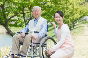 Senior on a wheelchair accompanied by a caregiver