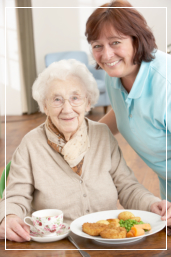 Senior about to have her meal assisted by a nurse
