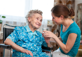 Caregiver giving a senior a glass of water